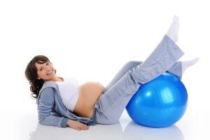 Mulher grávida fazendo exercícios físicos na bola